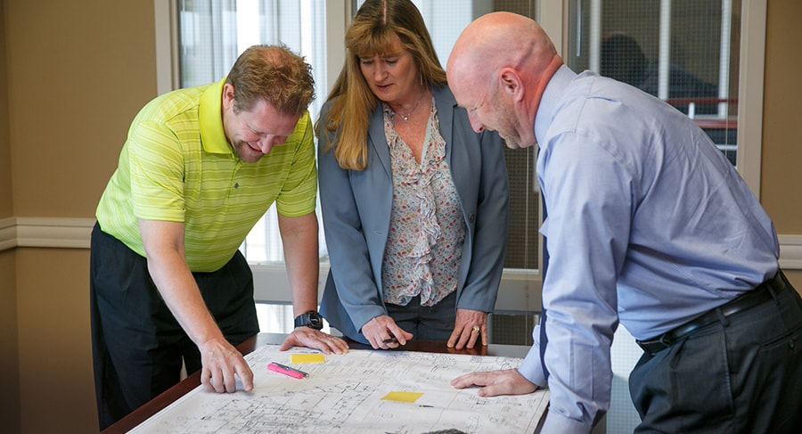 Horst Management Services employees collaborating around a blueprint